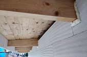 Installation Of Wooden Beams Of Roof Frame With Spray Foam On A House Wall Under Construction. poster