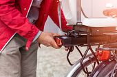 Man inserting battery in backseat of electric bicycle  poster