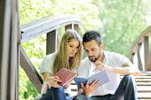 Beautiful couple reading book outdoors