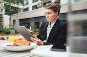 Female Creative Freelancer Working On Digital Tablet While Coffee Break At Veranda On Cafe. Business poster