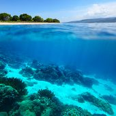 Collage of underwater coral reef and sea surface with green island on the horizon