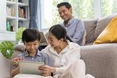Happy Asian Family Spending Time Together On Sofa In Living Room. Family And Home Concept poster