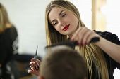 Young Woman Barber Cutting Client Hair In Salon. Hairdresser Holding Scissors And Hairbrush. Beautif poster