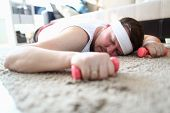Exhausted Man Lay On Floor With Dumbbells In Hands. Sportsman Sleep In Apartment And Hold Sports Equ poster