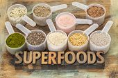 superfoods word in letterpress wood type with plastic scoops of healthy seeds and powders (chia, fla