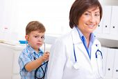 pic of 55-60 years old  - 3 years old boy playing with senior female doctor at office - JPG