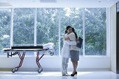 picture of stretcher  - Doctor and patient hugging in a hospital next to a stretcher - JPG