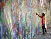 Person Adding Grafitti To The John Lennon Wall