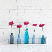 stock photo of vase flowers  - Decorative shelf on white brick wall with flowers in vase on it - JPG