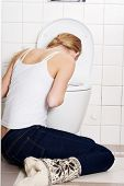 pic of female toilet  - Young caucasian woman is vomiting in the bathroom - JPG