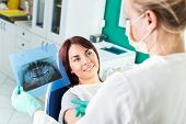 picture of roentgen  - Young female dentist showing X - JPG