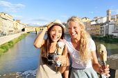 Happy women friends eating ice cream on travel in Florence. Cheerful girlfriends enjoying italian fo