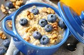 picture of porridge  - Oatmeal with fresh blueberries over a rustic wooden background - JPG