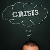 a man over a blackboard with a thought bubble drawn in it and the word crisis, depicting the idea of