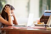 image of 13 year old  - Stressed Teenage Girl Using Laptop On Desk At Home - JPG