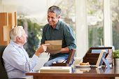 stock photo of keepsake  - Senior Father Discussing Document With Adult Son - JPG