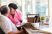 stock photo of keepsake  - Senior Couple Putting Letter Into Keepsake Box - JPG
