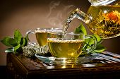 stock photo of teapot  - horizontal photo of the glass teapot flow green tea in cup on brown background tea ceremony - JPG