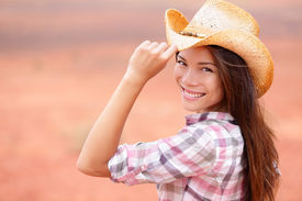 stock photo of cowgirls  - Cowgirl woman smiling happy on american prairie wearing cowboy hat - JPG