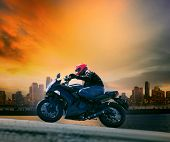 picture of motorcycle  - young man and safety suit riding big motorcycle against beautiful dusky sky and urban scene with copy space