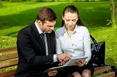 picture of work bench  - Young Business couple sitting on the bench and reading or working with tablets outdoors - JPG