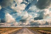 image of farm land  - Empty country road with dramatic cloudy sky - JPG