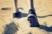 picture of girl walking away  - girl feet in sneakers go away on the sand - JPG