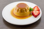 image of custard  - Creme caramel vanilla custard dessert or flan on white dish with strawberry in the table - JPG