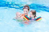 stock photo of floaties  - Young Active Mother Having Fun In A Swimming Pool With Two Kids  - JPG