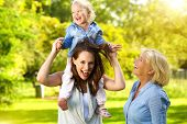 stock photo of grandmother  - Portrait of a happy mother with child and grandmother having fun outdoors - JPG