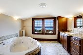 stock photo of tub  - Luxury bathroom with whirlpool brown cabinet and white whirlpool bath tub - JPG