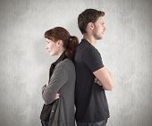 stock photo of irritated  - Irritated couple ignoring each other against weathered surface - JPG