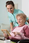 stock photo of disability  - Elder disabled woman holding frame with picture - JPG