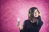 image of mood  - Young happy girl listening to music with headphones and mp3 player with eyes closed - JPG