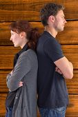 stock photo of irritated  - Irritated couple ignoring each other against overhead of wooden planks - JPG