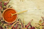 foto of pepper  - Wooden spoon of cayenne pepper in bowl with cayenne pepper on wooden table - JPG