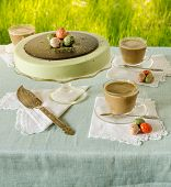stock photo of cheesecake  - Easter table with tea matcha cheesecake and white coffee on background of green grass - JPG