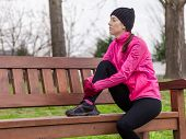 stock photo of sitting a bench  - Sad young female athlete sitting on a bench on a cold winter day in the track of an urban park - JPG