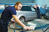 stock photo of garage  - Automobile glazier adding glue on windscreen or windshield of a car in auto service station garage before installation - JPG