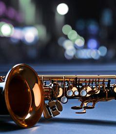 image of wind instrument  - black saxophone before a window in nightclub - JPG
