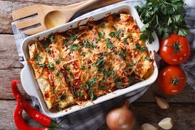 foto of enchiladas  - Mexican enchilada in a baking dish with the ingredients on the table close - JPG