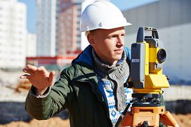 picture of geodesic  - Surveyor builder worker with theodolite transit equipment at construction site outdoors during surveying work - JPG
