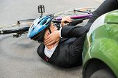 picture of accident victim  - Male Cyclist With Neck Pain Lying On Street After Road Accident - JPG