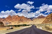 foto of jammu kashmir  - A concrete road towards beautiful rocky mountains and blue sky with peaks of Himalaya Leh Ladakh Jammu and Kashmir India - JPG