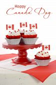 stock photo of flag confederate  - Happy Canada Day celebration cupcakes with red and white maple leaf flag on red cake stand against a white background vertical with sample text - JPG