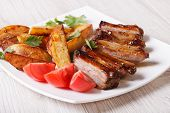 stock photo of baby back ribs  - Pork ribs potatoes and tomatoes on a plate close - JPG