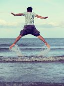 image of jumping  - Jump to the freedom Asian man jumping on the beach retro and vintage tone - JPG