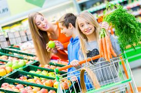stock photo of grocery cart  - Family selecting fruits and vegetables while grocery shopping in supermarket  - JPG