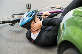 foto of accident victim  - Male Cyclist With Neck Pain Lying On Street After Road Accident - JPG