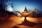 Magic lamp in the desert from the story of Aladdin with Genie appearing in blue smoke concept for wi poster